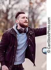 Hipster man standing next to a car