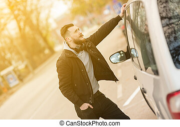 Hipster man standing next to a car