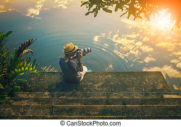 hipster man taking a photograph on pier against beautiful skies reflect on lake