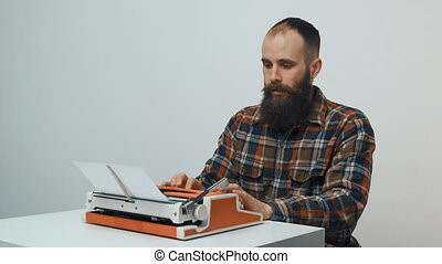 Hipster man typing with a red vintage typewriter