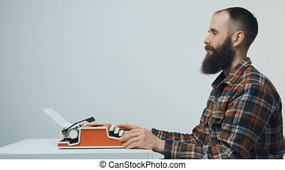 Hipster man typing with a red vintage typewriter - Side view...