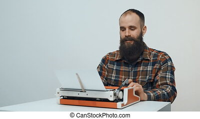 Hipster man typing with a red vintage typewriter smiling and...