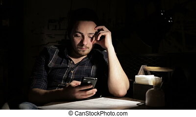 Hipster man using smartphone in cafe in the night