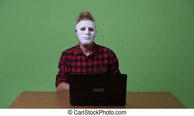 Hipster man wearing mask as hacker against wooden table