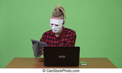 Hipster man wearing mask as hacker while multi-tasking work against wooden table