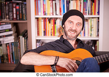 Hipster man with beard and hat playing guitar sitting on a couch in front of books