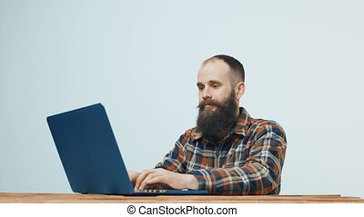 Hipster man working with laptop - Bearded hipster man...