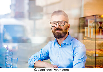Hipster manager sitting in cafe by the window, reflection