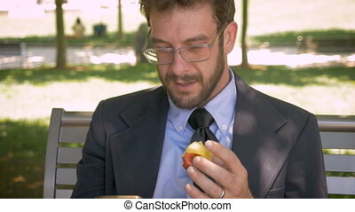 Hipster millennial man takes a bite out of an apple while on his smart phone