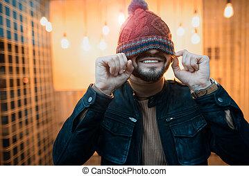 hipster, niño, sonriente, con, el, sombrero, encima, el suyo, ojos, contra, el, plano de fondo, de, lamps.
