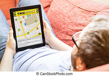 hipster on the sofa with taxi app tablet