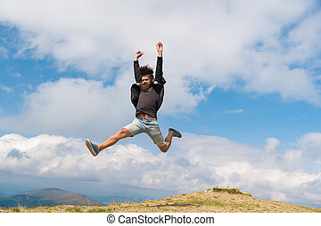 Hipster or brutal macho conquers mountain. Man with brutal appearance jumps. Freedom concept. Man with beard enjoy freedom, jumpimg on top of mountain. Hipster feels free while hiking, sky background