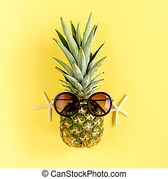 Hipster pineapple in sunglasses on yellow background. Summer background. Flat lay