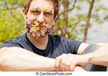 young self-confident man looking at camera with his eyebrow and beard disguised with flowers