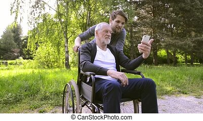 Hipster son and father in wheelchair at park taking selfie.