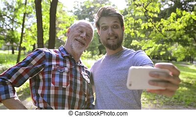 Hipster son and his senior father in park taking selfie.