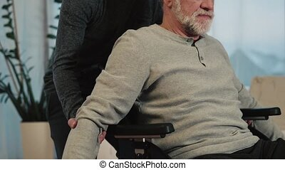 Hipster son and his senior father in wheelchair at home.,...
