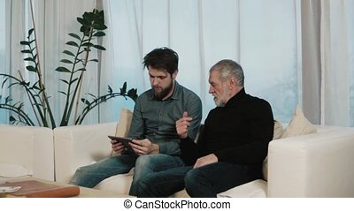 Hipster son and his senior father with tablet at home. Two...
