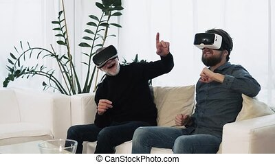 Hipster son and his senior father with VR goggles at home....