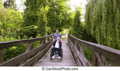 Hipster son walking with disabled father in wheelchair in the park.