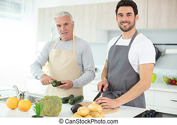 hipster son with his senior father cooking in the kitchen