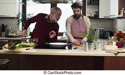Hipster son with his senior father cooking in the kitchen....