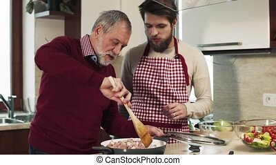 Hipster son with his senior father cooking in the kitchen.