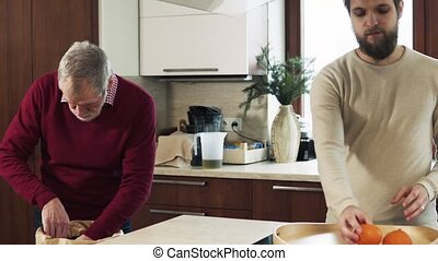 Hipster son with his senior father in the kitchen. Two...