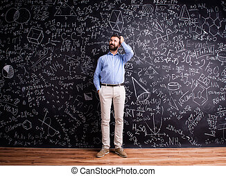 Hipster teacher against big blackboard with mathematical...