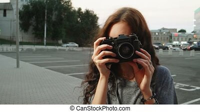 Hipster teenager with vintage camera smiling in the street