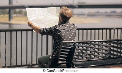 Hipster tourist is looking at the map of Europe, telling where to go.