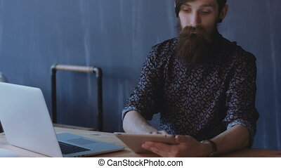 Hipster using notepad. - Adult hipster with big beard and...