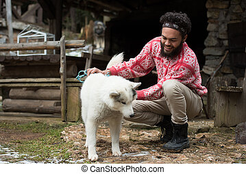 hipster with dog in front of wooden house
