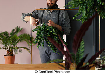 Hipster with hobby cutting leaves of plant in the orangery