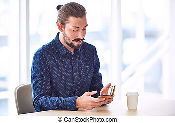 Hipster with man bun using his phone seated at table