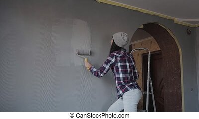 Hipster woman decorates her home painting the wall in her bedroom in gray with a roller. The girl holds a roller in the hands and pains the walls in the room