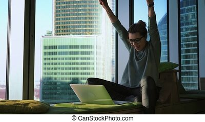 Hipster woman freelancer is working on her laptop at home by the panoramic window and is celebrating success with raised arms