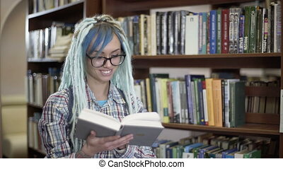 Hipster woman in glasses with dreadlocks smiling and reading...