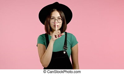 Hipster woman in hat holding finger on her lips over pink ...