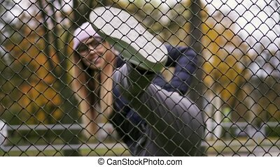 Hipster woman looks over the fence and kicks. Slow Mo.