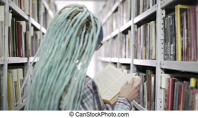Hipster woman reading book in college library while standing...