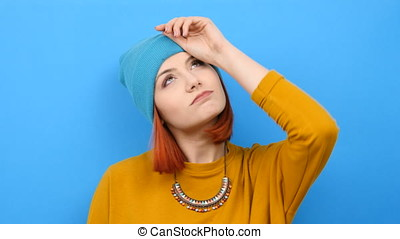 Hipster woman wearing a blue hat puts her hand on the head...