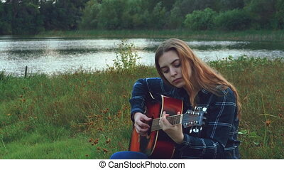 Hipster young beautiful girl, embraced by a creative start in a forest glade at noon, inspired by a forest landscape with a view of the river and simply amazing nature, picks up a new melody for a new song. 4k.