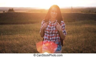 Hipster young girl walk with backpack enjoying sunset on...