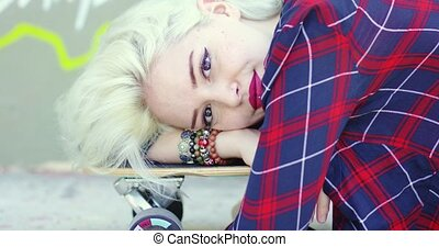 Hipster young woman lying on a skate board