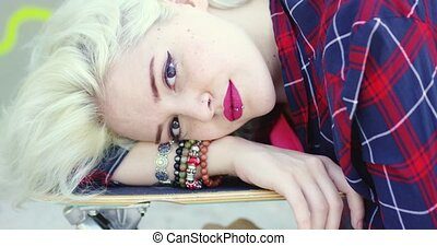 Hipster young woman lying on a skate board - Hipster young...