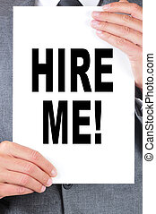 hire me - a man wearing a suit holding a signboard with the...
