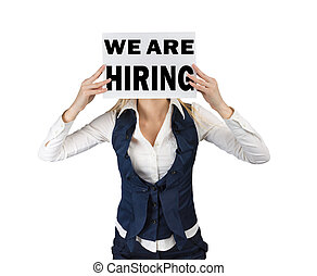 White woman holds sheet of paper ad at head level with text we are hiring