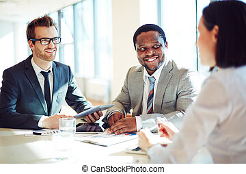 Hiring employee - Smiling businessmen listening to young...