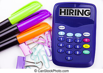 Hiring text in the office with surroundings such as marker, pen writing on calculator. Business concept for Recruitment and Job recruiting advertisement white background with copy space